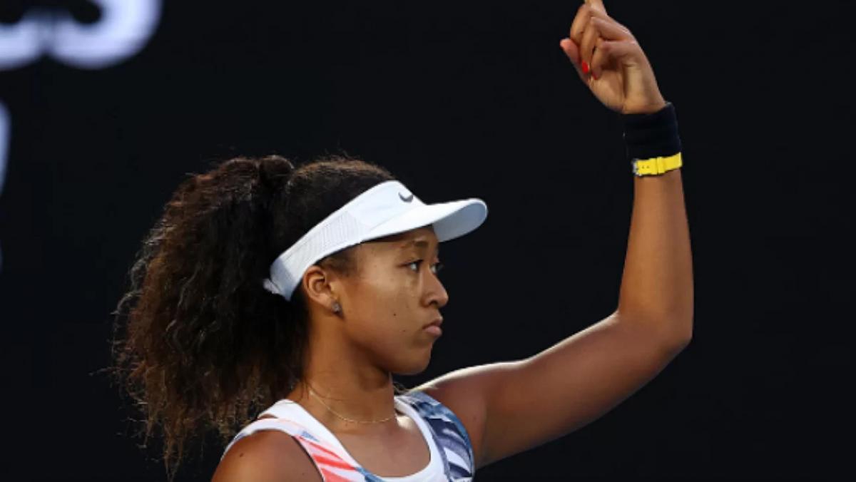 immagine di profilo della tennista Naomi Osaka con un braccio alzato
