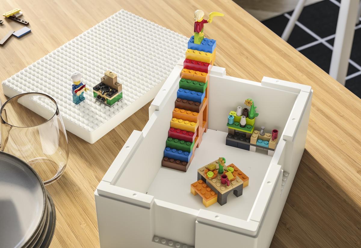 vista dall'alto di una scatola BYGGLEK collezione tra IKEA e LEGO, una scaletta di lego con in cima un personaggio della lego, dentro la scatola un tavolo di lego e sul lato una cucina di lego