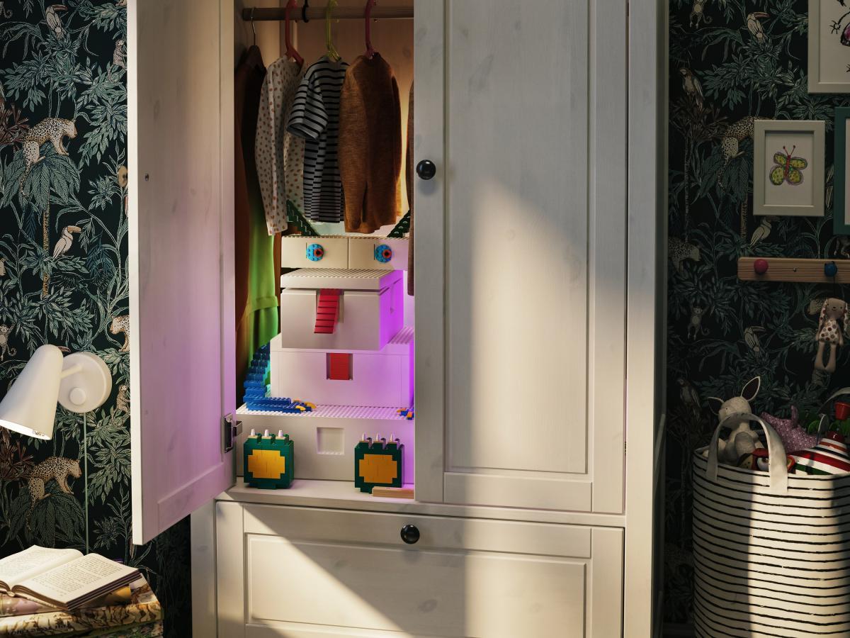 vista di una camera, in primo piano una armadio con l'anta di sinistra aperta, dentro si vedono le scatole LEGo IKEA BYGGLEK con alcuni dettagli di LEGO arraccati