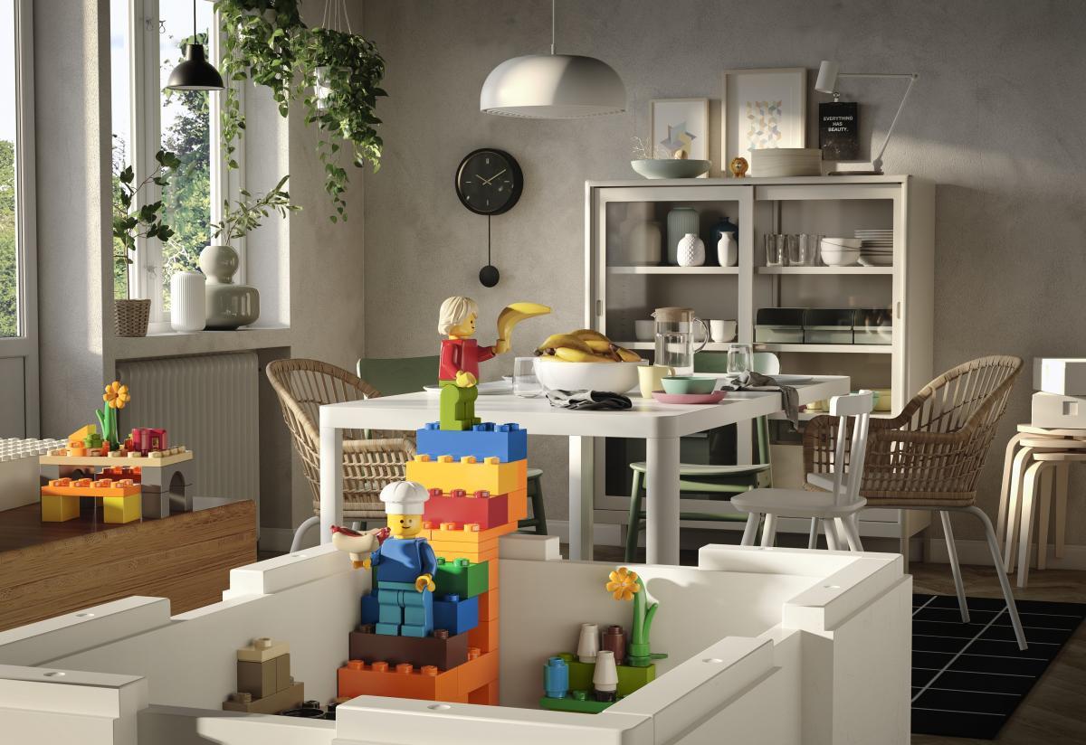 in primo piano una scatola IKEA LEGo BYGGLEK sullo sfondo una sala da pranzo con tavolo e dispensa