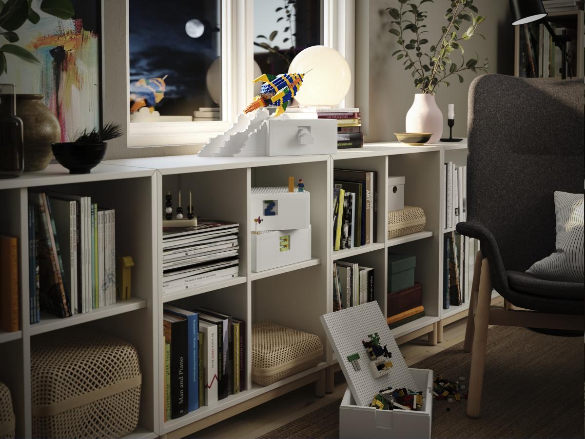 Ambiente interno di una casa dove si vede un mobile su cui è appoggiata una scatola IKEA LEGO BYGGLEK con applicata sul coperchio una costruzione lego a forma di razzo