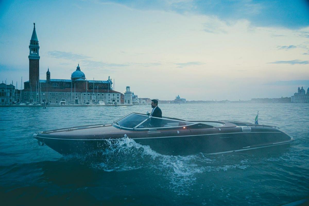 Pierfrancesco Favino durante le riprese de cortometraggio a Venezia mentre guida un motoscafo Riva
