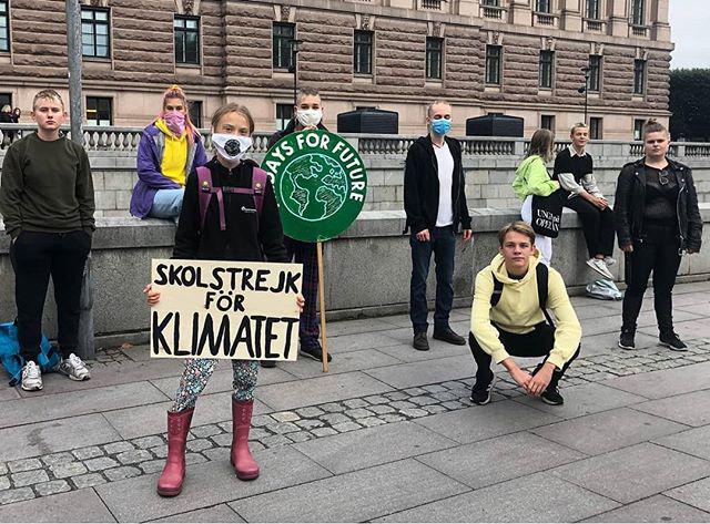 Greta Thunberg con in mano il cartello iconico contro il cambiamento climatico davanti al parlamento svedese, intorno a lei altri ragazzi