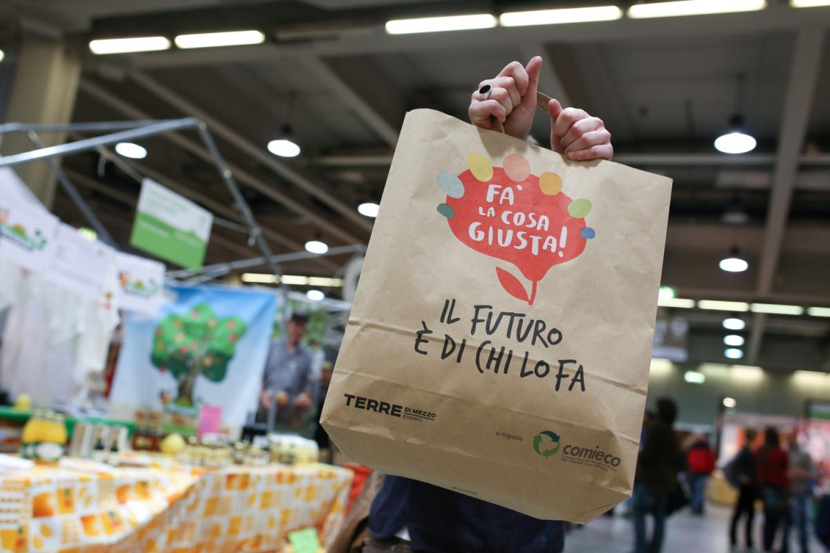 in primo piano un sacchetto in carta della manifestazione Fà la cosa giusta