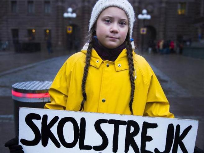 Greta Thunberg in una delle sue prime immagini con l'impermeabile giallo, le trecce e il cartello iconico