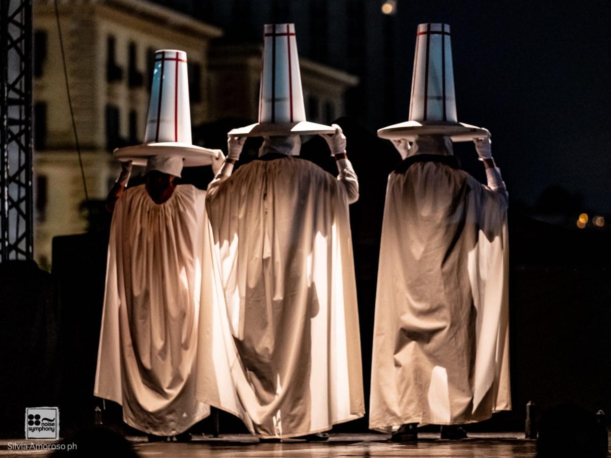 Asterione in scena il 12 ottobre al Teatro Sannazaro di Napoli tre attori di spalle sulla scena con abiti lunghi bianchi e grandi cappelli