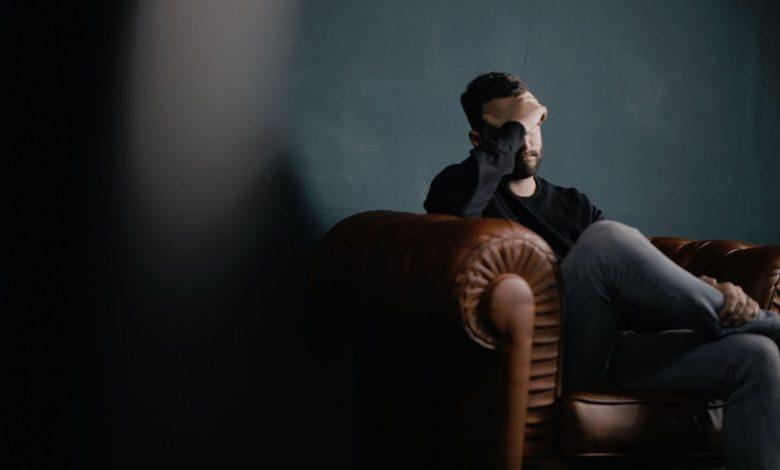 paura del rimpianto uomo seduto sul divano che riflette