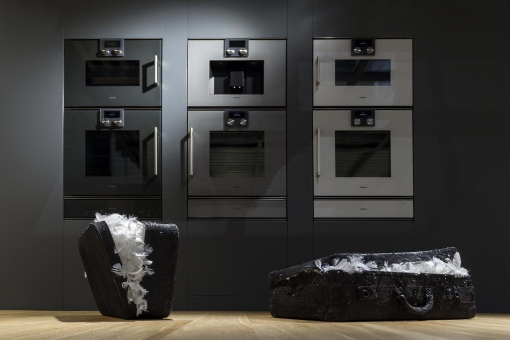 Julia Bornefeld, opera dell'artista tedesca con valigie di carbone contenenti piume bianche