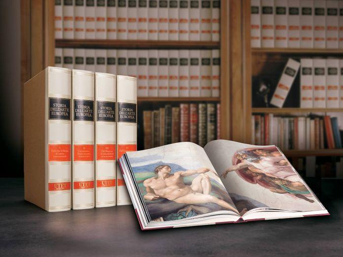 Utet grandi opere un libro aperto e alcuni cataloghi di pregio, sullo sfondo una libreria