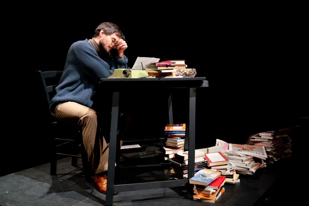 Mattatoio n.5 attore sul palco seduto alla scrivania
