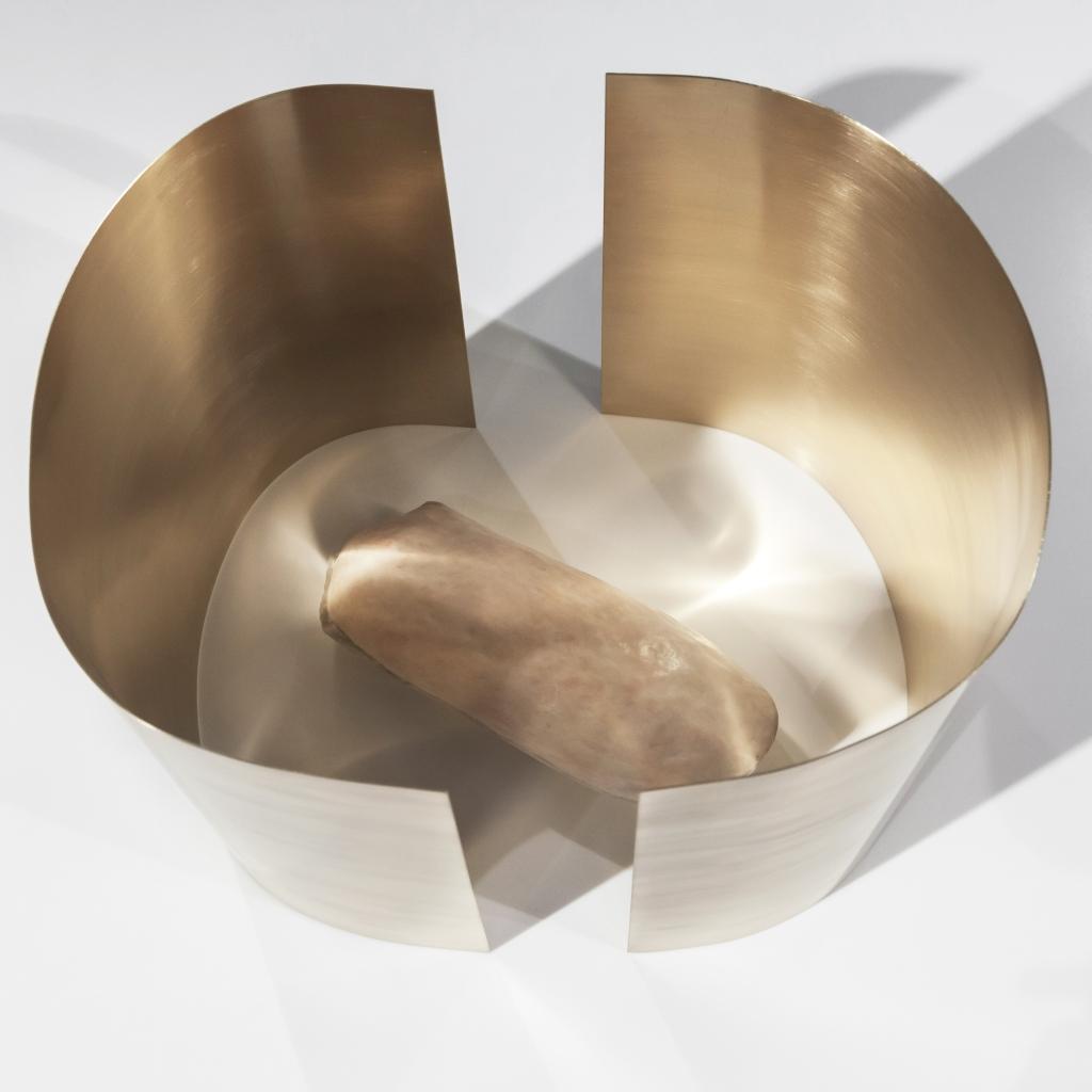 scultura in metallo a tubo che racchiude forma organica di cera