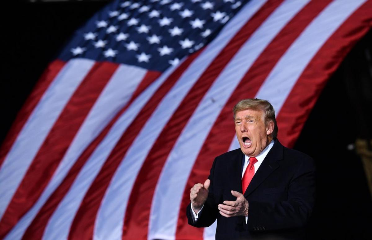 l'epilogo della presidenza Trump che urla, bandiera americana alle sue spalle