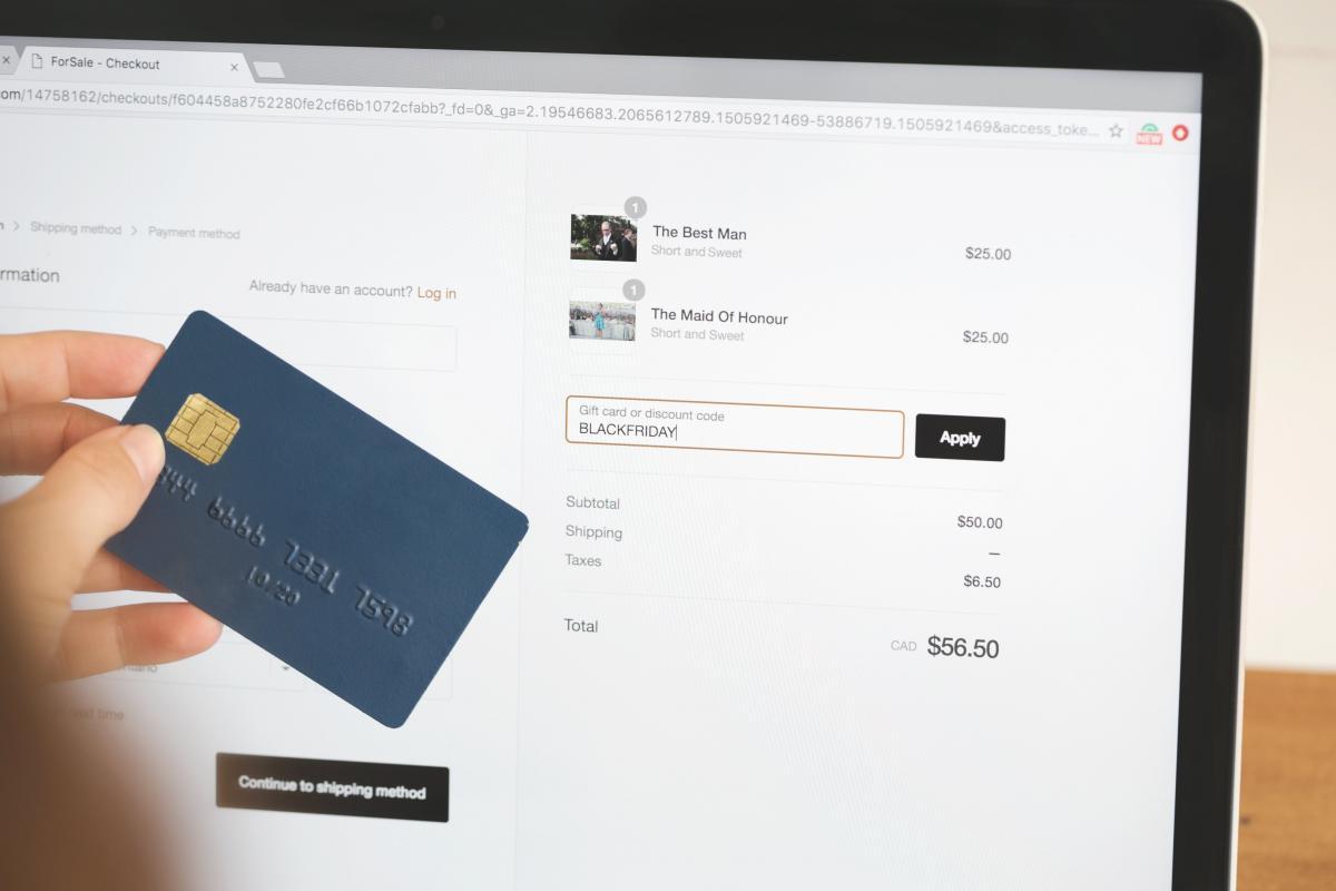 Donna tiene in mano carta di credito e si appresta a completare un acquisto online