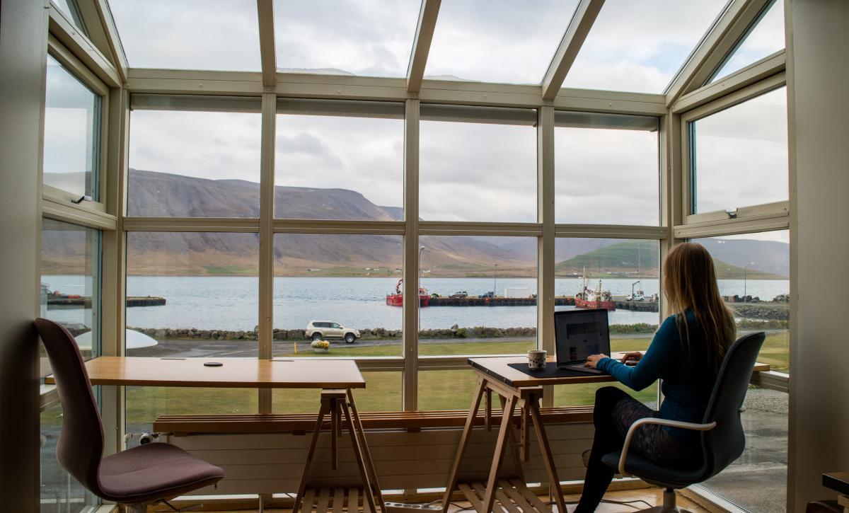 Ragazza seduta ad una scrivania lavora con un computer portatile dentro a un vano open space con visuale su un lago