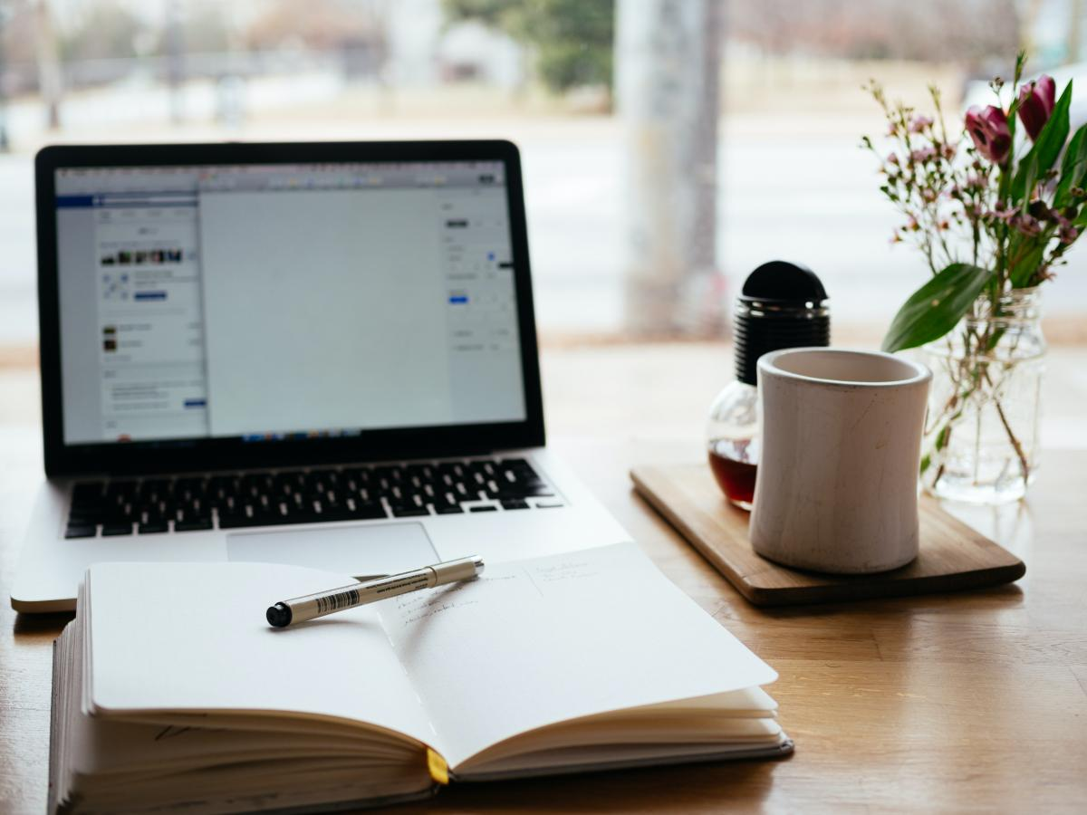 I migliori lavori da fare in smart working Quaderno aperto con una penna sopra e sullo sfondo un computer portatile aperto su una schermata bianca con una tazza di caffè sulla destra