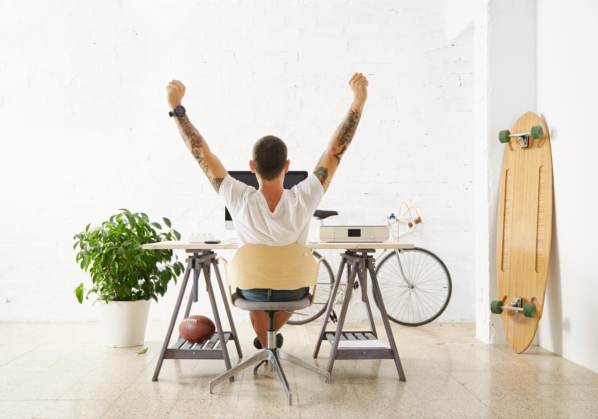 Giovane tatuato lavora da remoto e siede di spalle nel suo ufficio circondato dai suo hobby: uno skateboard, una bicicletta e una pianta.