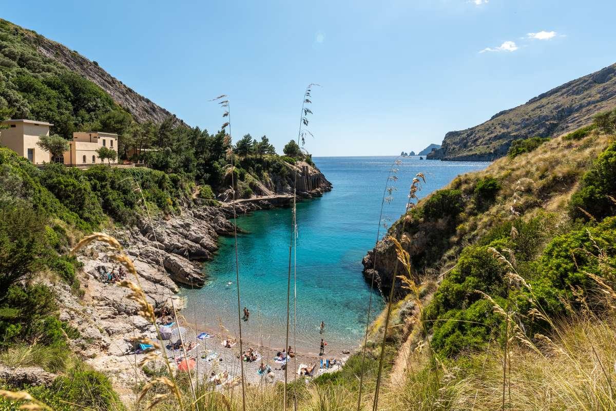 Le più belle spiagge del sud Italia: la Baia di Ieranto vista dall'alto, con i faraglioni di Capri in lontananza