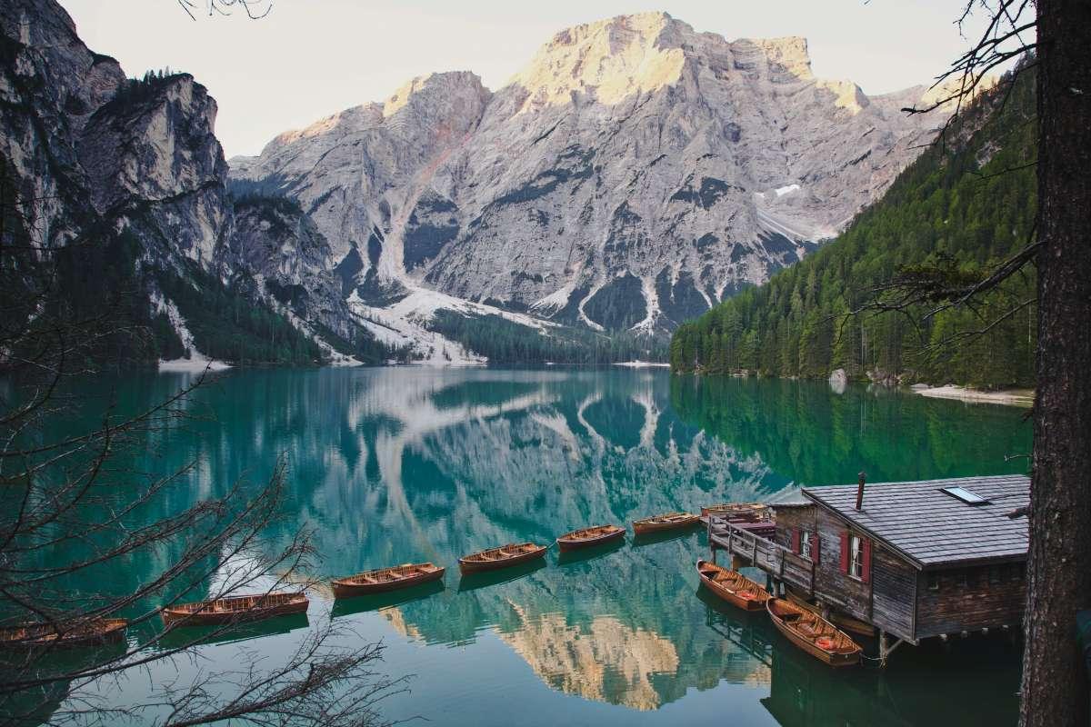 I migliori laghi italiani: immagine panoramica del lago di Braies, con le dolomiti innevate sullo sfondo e riflesse nelle acque verde smeraldo