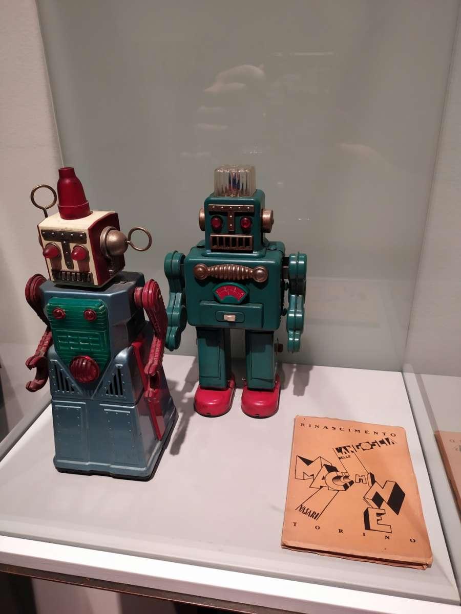 2 robot giocattolo e un libro , ventrina della mostra Pianeta città alla Fondazione Ragghianti di Lucca