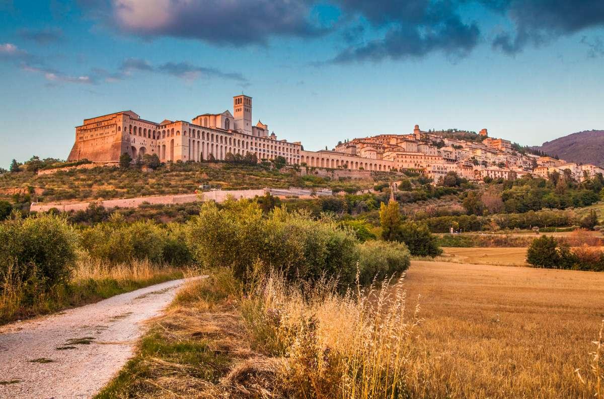 Foto panoramica di Assisi al tramonto con la Basilica di San Francesco in primo piano
