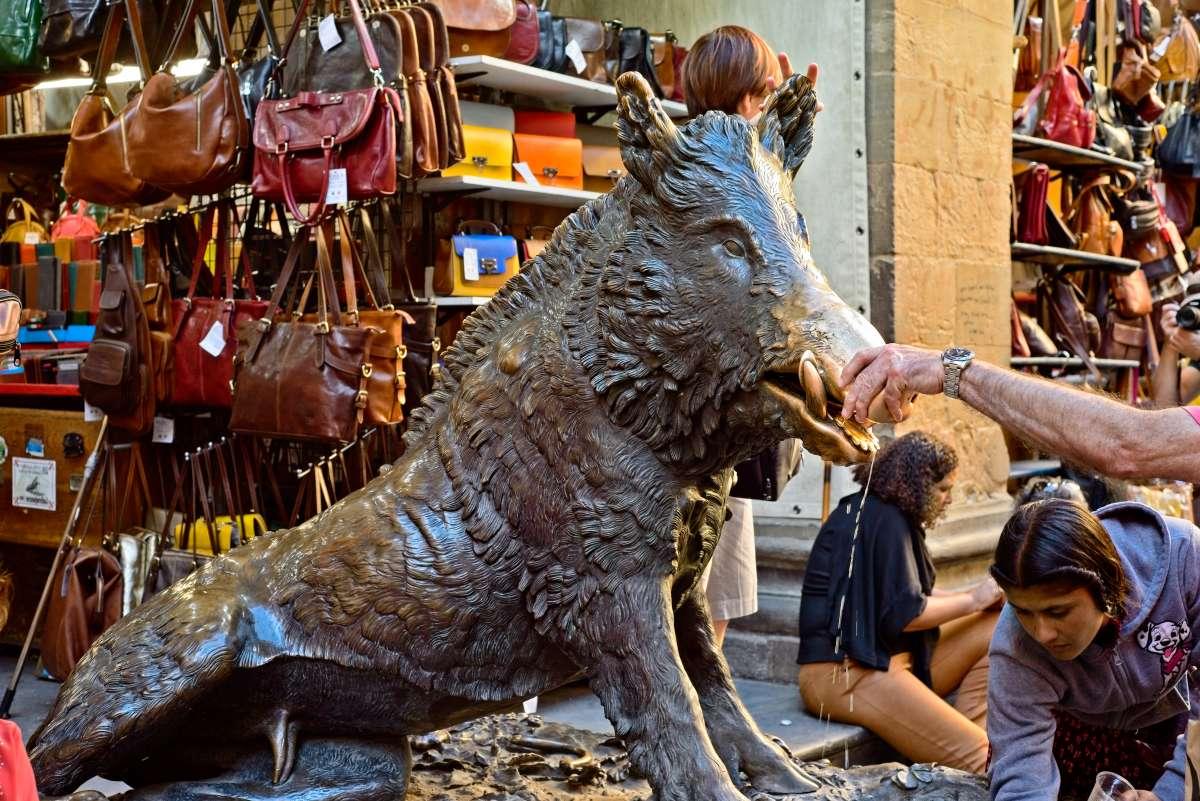 Firenze insolita: la Fontana del Porcellino all'interno del Mercato di Loggia nuova mentre un turista inserisce una monetina all'interno della bocca della scultura